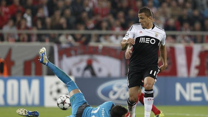 Olympiakos' goalkeeper Roberto, left, saves the ball in front of Benfica's Lima during a Champions League group C soccer match between Olympiakos and Benfica at Karaiskaki stadium, in Piraeus, near Athens, Tuesday, Nov. 5, 2013