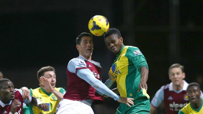 West Ham United's Tomkins challenges Norwich City's Yobo during their English Premier League soccer match at the Boleyn Ground in London