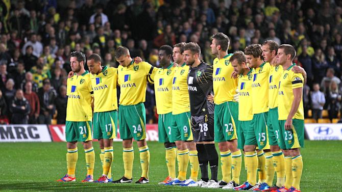 Norwich City players observe a minutes silence in memory of former manager John Bond