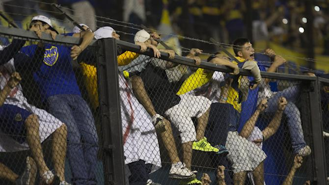 BOca Junior' fans climb the fence to cheer their team during an Argentina's league soccer match against Rosario Central  in Buenos Aires, Argentina, Sunday, Oct. 13, 2013