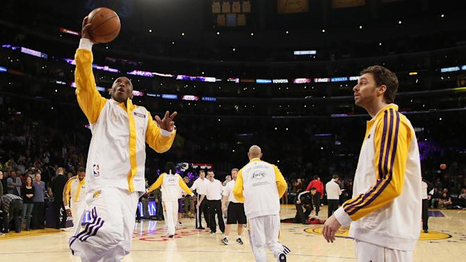 Los Angeles Lakers' Kobe Bryant makes his first layup in warm-ups as Pau Gasol, right, of Spain, looks on before the NBA basketball game against the Toronto Raptors  in Los Angeles, Sunday, Dec. 8, 2013. Bryant is expected to make his long-awaited return from a torn left Achilles tendon injury from April 12th