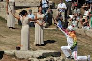 Greek actress Ino Menegaki (fourth left) passes the Olympic Flame to the first torch bearer Greek skier Giannis Antoniou on September 28, 2013 in ancient Olympia