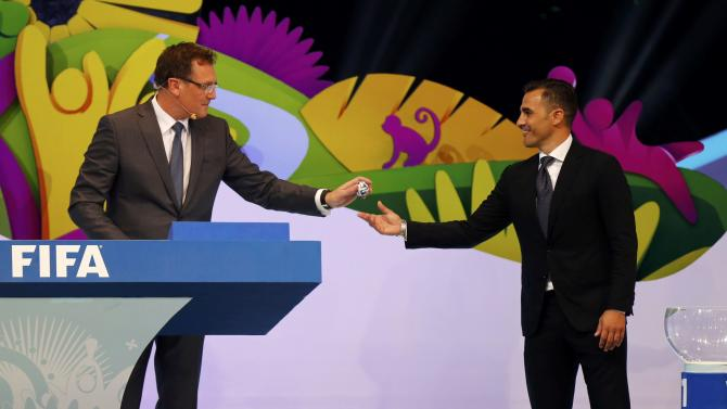 Former Italy soccer player Cannavaro hands a ball that he had drawn from a pot to FIFA Secretary General Valcke during the draw for the 2014 World Cup at the Costa do Sauipe resort in Sao Joao da Mata