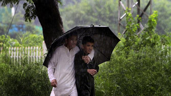Pakistani boys share an umbrella as rain pours in Islamabad, Pakistan, Tuesday, Aug. 6, 2013. (AP Photo/Anjum Naveed)