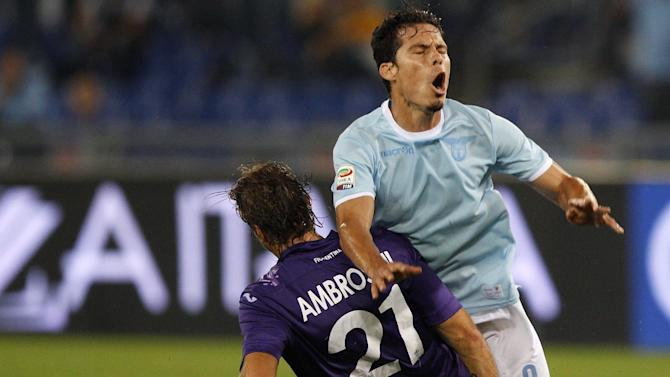 Lazio midfielder Hernanes, of Brazil, right, is fouled by Fiorentina midfielder Massimo Ambrosini during a Serie A soccer match between Lazio and Fiorentina, at Rome's Olympic stadium, Sunday, Oct. 6, 2013