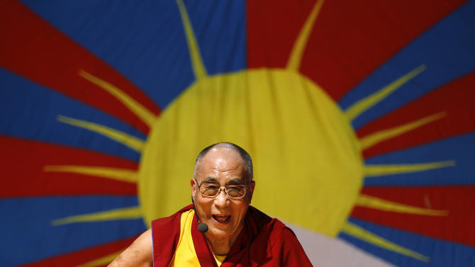 """FILE - In this Nov. 27, 2012 file photo, Tibetan spiritual leader the Dalai Lama laughs as he addresses Tibetan exiles living in Bangalore, in front of the Tibetan flag, in Bangalore, India. The Dalai Lama is set to headline India's Jaipur Literature Festival to speak about faith with one of his biographers, Pico Iyer. The Tibetan spiritual leader will hold a session on the festival's first day, Thursday, Jan. 24, 2013, titled: """"Kinships of Faiths: Finding the Middle Way."""" (AP Photo/Aijaz Rahi, File)"""