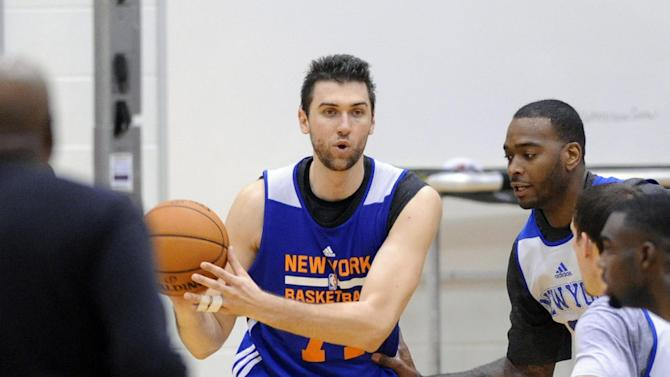 New York Knicks' Andrea Bargnani, of Italy, handles the ball as coach Mike Woodson, left, looks on during NBA basketball training camp Tuesday, Oct. 1, 2013, in Greenburgh, N.Y