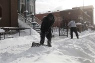 Laborers shovel the snow off of the sidewalk in the midtown neighborhood of Detroit, Michigan January 6, 2014. REUTERS/Rebecca Cook