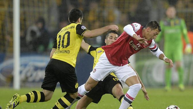 Dortmund's Henrikh Mkhitaryan, left, and Arsenal's Mesut Ozil challenge for the ball during the Champions League group F soccer match between Borussia Dortmund and Arsenal FC in Dortmund, Germany, Wednesday, Nov. 6, 2013