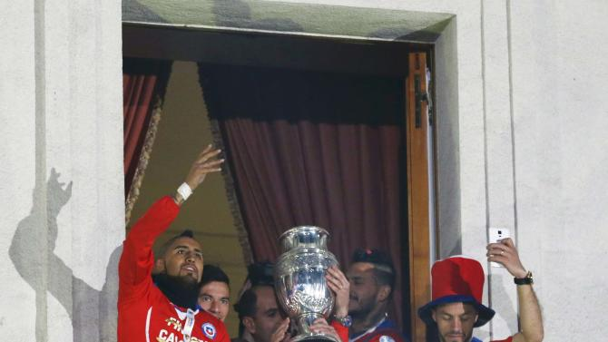 Chile's Arturo Vidal waves to the crowd while holding the trophy with teammates on the balcony of the La Moneda presidential palace