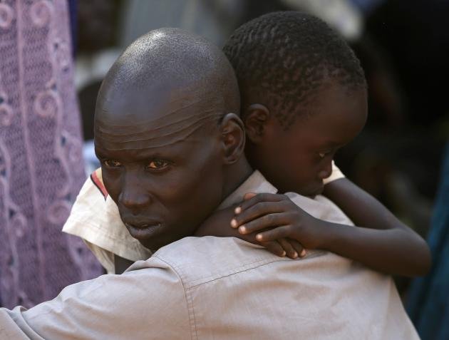 An internally displaced man holds his son inside UNMIS compound in Juba