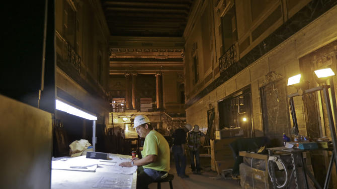 Robert Junker, a construction superintendent, looks over plans as workers perform renovation work at the Saenger Theater in Downtown New Orleans on Wednesday, May 22, 2013. (AP Photo/Gerald Herbert)