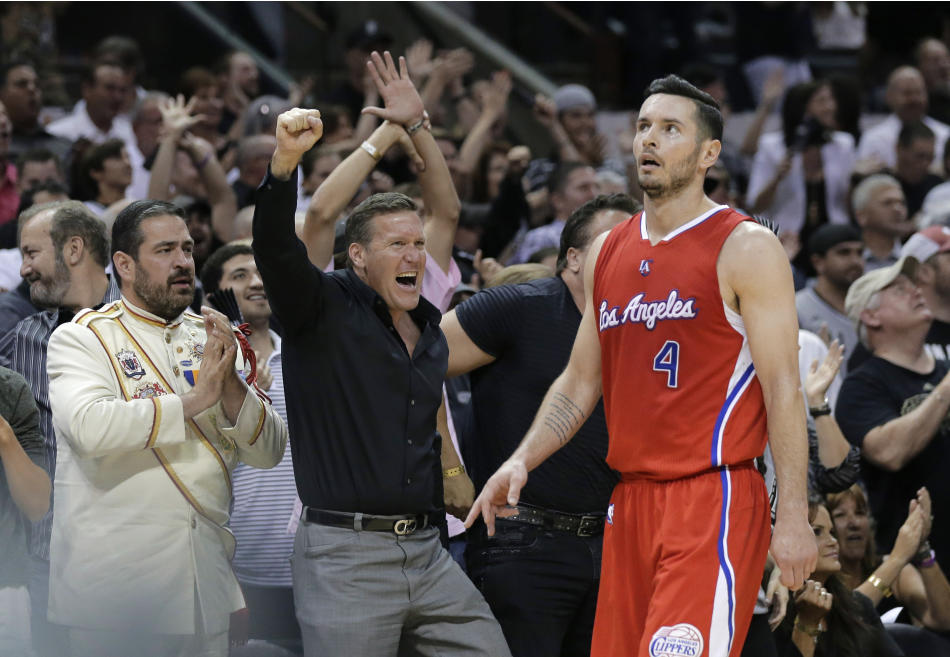 Los Angeles Clippers' J.J. Redick (4) walks past cheering San Antonio Spurs fans during the first half of Game 3 in an NBA basketball first-round playoff series, Friday, April 24, 2015, in San Ant