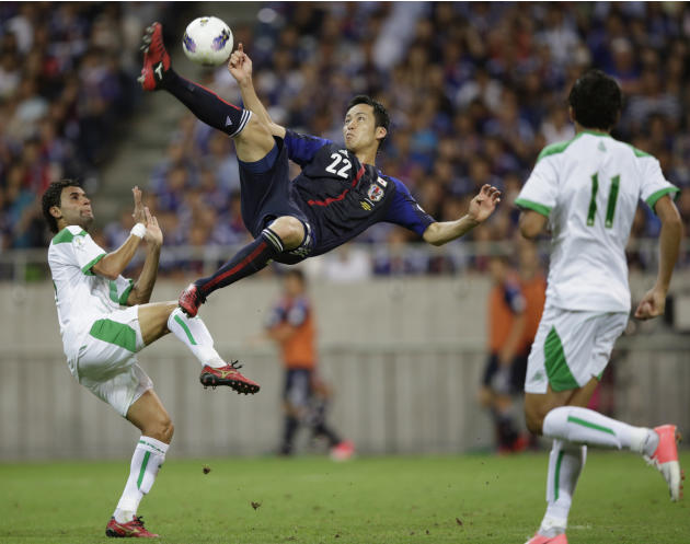 Japan's Yoshida shoots the ball between Iraq's Salim and Al-Janabi during their 2014 World Cup qualification soccer match in Saitama