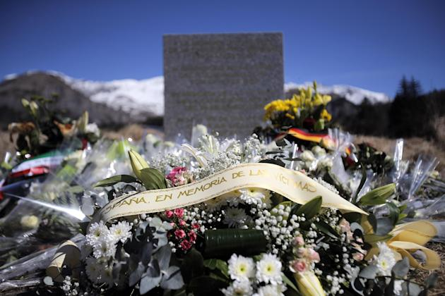 A stele and flowers laid in memory of the victims are placed in the area where the Germanwings jetliner crashed in the French Alps, in  Le Vernet, France, Friday, March 27, 2015. The crash of Germanwi