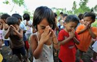 Young Filipino children pray during a religious service near the town of Guinobatan in 2009. The Philippines leads the world in the number of people who believe in God, while the elderly across all countries tend to be the most religious, according to a US study out Wednesday