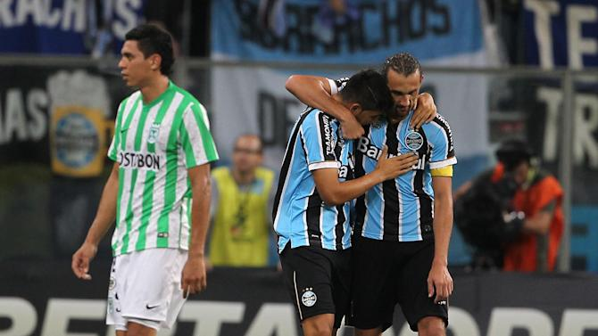 Alan Ruiz of Brazil's Gremio, center, celebrates his goal accompanied with teammate Hernan Barcos during their game against Colombia's Atletico Nacional at the Copa Libertadores in Porto Alegre, Brazil, Tuesday, Feb.25, 2014. Gremio won 3-0