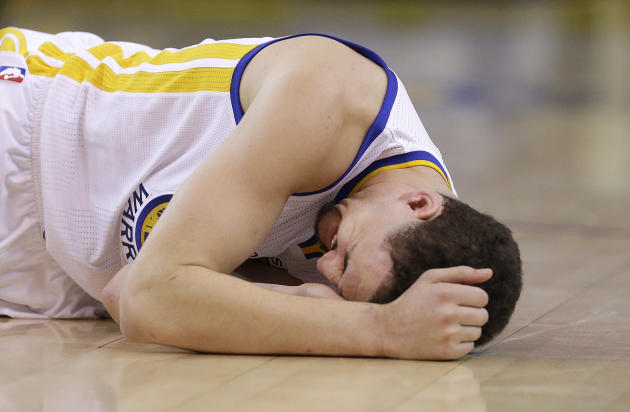 In this photo taken May 27, 2015, Golden State Warriors guard Klay Thompson reacts after taking a knee to his head from Houston Rockets forward Trevor Ariza during the second half of Game 5 of the NBA