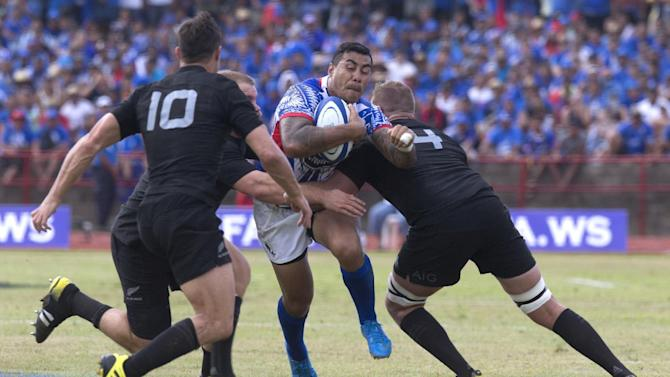 Samoa's Tusiata Pisi, center, tries to run through a defense of New Zealand All Blacks during their rugby union match at Apia Park in Apia, Samoa, Wednesday, July 8, 2015. New Zealand won the match 25-16 in the All Blacks' first-ever test match in the Pacific Island nation. (Dean Purcell/New Zealand Herald via AP) NEW ZEALAND OUT, AUSTRALIA OUT