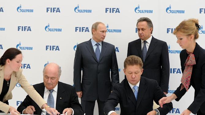 Russian President Vladimir Putin, center, attends a signing ceremony of a partnership agreement between  FIFA and Gazprom in the Black Sea resort of Sochi, Russia, Saturday, Sept. 14, 2013. The agreement was signed by FIFA President Sepp Blatter, left, and  Russian gas monopoly Gazprom Head Alexei Miller, right. At right in the background is Russian Sports Minister Vitaly Mutko
