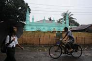 "This file photo shows local residents passing a mosque in Sittwe, capital of Myanmar's western Rakhine state. Buddhist villagers fled their homes Saturday as renewed sectarian violence hit western Myanmar, officials said, blaming Muslim Rohingya people from a ""neighbouring country"" for the unrest"