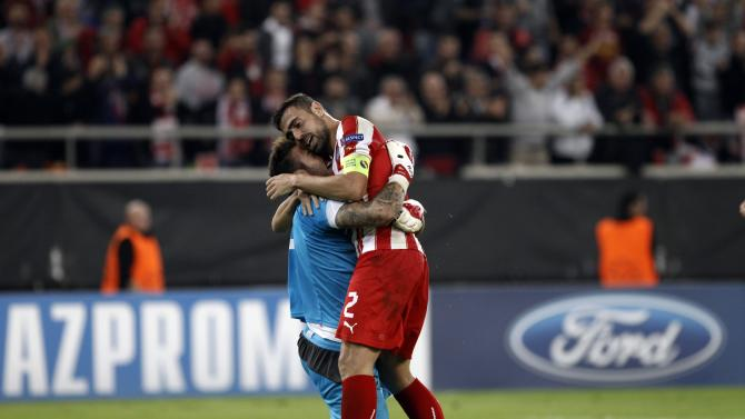 Olympiakos Piraeus' goalkeeper Roberto and his teamate Giannis Maniatis celebrate after beating Benfica during their Champions League soccer match in Piraeus