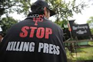 A Myanmar journalist wears a T-shirt reading 'Stop killing press' as he waits outside a court for a ruling on a defamation case against 'The Voice Weekly' in Yangon on August 23, 2012. The mining ministry filed a criminal defamation suit against The Voice Weekly, which reported that the auditor-general's office had discovered misappropriations of funds and fraud at the government division