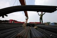A worker unloads steel bars outside a factory in Huaibei, east China's Anhui province. China's exports grew 1% in July year-on-year to 176.9 billion USD, official data showed on August 10, in a fresh sign of weakness in the world's second-largest economy