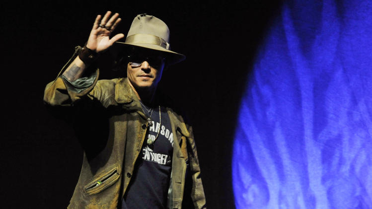 "Johnny Depp, who plays Tonto in the upcoming film ""The Lone Ranger,"" makes a surprise appearance onstage at  the Walt Disney Studios presentation at CinemaCon 2013 at Caesars Palace on Wednesday, April 17, 2013 in Las Vegas. (Photo by Chris Pizzello/Invision/AP)"