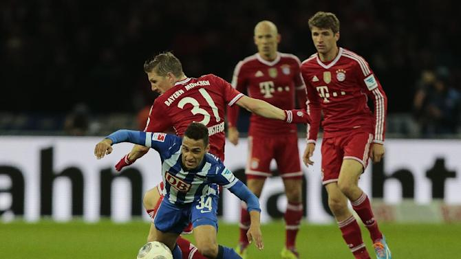 Berlin's Hany Mukhtar, front, and Bayern's Bastian Schweinsteiger challenge for the ball when Bayern's Thomas Mueller, right, and Bayern's Arjen Robben of the Netherlands look on during the first division Bundesliga soccer match between Hertha BSC and FC Bayern Munich in Berlin, Tuesday, March 25, 2014