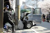 Police officers in Japan inspect a minivan which crashed into a telephone pole after hitting a crowd of pedestrians in the temple-spotted ancient capital of Kyoto on April 12. Eight people died when an apparently epileptic driver crashed the minivan into a crowd of pedestrians, officials and reports said