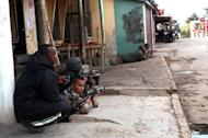 Members of the army and police take up positions during a mutiny by troops at a military camp near Madagascar's main airport in Antananarivo. Madagascar's army said Sunday it had put down a mutiny in a military camp Sunday, after clashes in which at least three people were killed