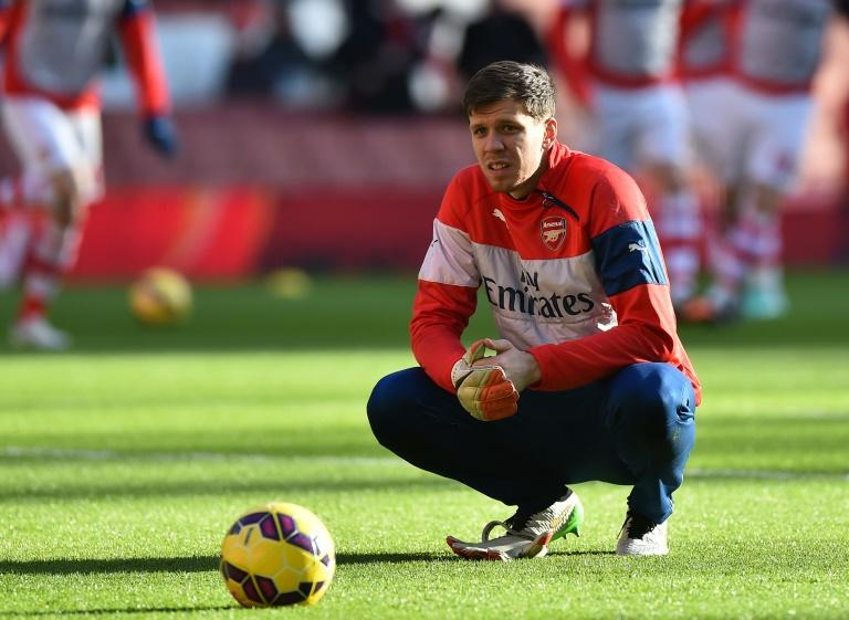 Goalkeeper Wojciech Szczesny takes a break during warm up ahead of the English Premier League football match between Arsenal and Stoke City at the Emirates Stadium in London on January 11, 2015