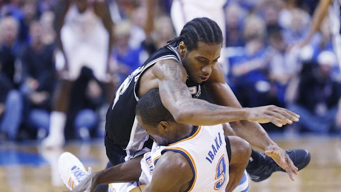 San Antonio Spurs forward Kawhi Leonard (2) lands on Oklahoma City Thunder forward Serge Ibaka (9) after the two chases a loose ball in the third quarter of an NBA basketball game in Oklahoma City, Wednesday, Nov. 27, 2013. Oklahoma City won 94-88