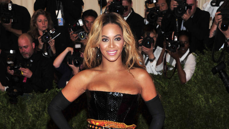 "FILE - This May 6, 2013 file photo shows singer Beyonce at The Metropolitan Museum of Art's Costume Institute benefit in New York. Beyonce has released her new album in an unconventional way: She announced and dropped it on the same day. The singer released ""Beyonce"" exclusively on iTunes early Friday, Dec. 13. (Photo by Charles Sykes/Invision/AP, File)"