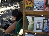 "A book street vendor passes the time on her smart phone as she waits for customers in Havana, Cuba, Tuesday, April 1, 2014. The Obama administration secretly financed a social network in Cuba to stir political unrest and undermine the country's communist government according to an Associated Press investigation. The project, dubbed ""ZunZuneo,"" slang for a Cuban hummingbird's tweet, lasted more than two years and drew tens of thousands of subscribers and sought to evade Cuba's stranglehold on the Internet with a primitive social media platform. First, the network would build a Cuban audience, mostly young people; then, the plan was to push them toward dissent. (AP Photo/Ramon Espinosa)"