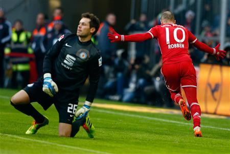 Braunschweig's goalkeeper Davari reacts while Bayern Munich's Arjen Robben celebrates after scoring a goal during their German first division Bundesliga soccer match in Munich