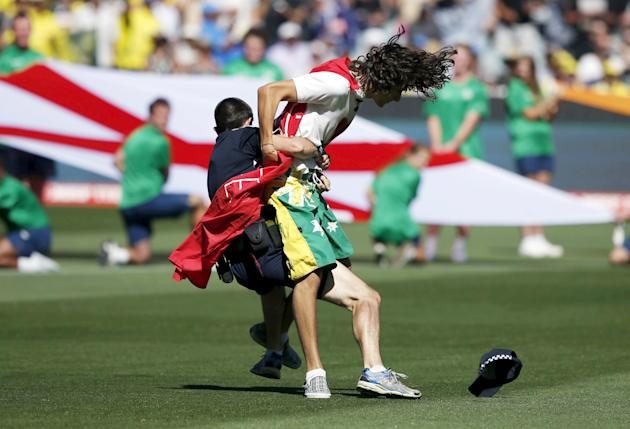 A policeman tackles a protester before the start of the Cricket World Cup final match between Australia and New Zealand at the MCG