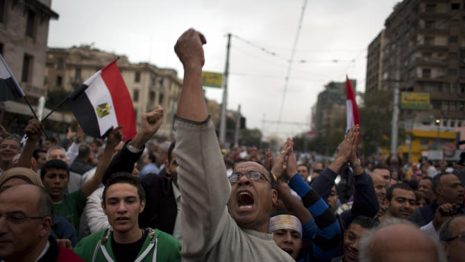 Egyptian protesters chant anti-Muslim Brotherhood slogans during a rally in front of the presidential palace, in Cairo, Egypt, Tuesday, Dec. 4, 2012. Egyptian riot police beefed up security around the presidential palace Tuesday ahead of a massive rally planned by activists protesting the Islamist leader's assumption of nearly unrestricted powers and a draft constitution hurriedly adopted by his allies. (AP Photo/Nasser Nasser)