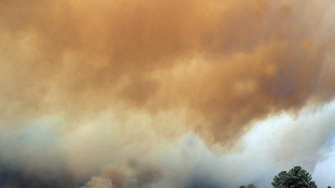 FILE - In this file photo taken Saturday, June 9, 2012, smoke billows from the Little Bear fire in southeastern New Mexico near Ruidoso, NM. When lightning sparks a wildfire deep in remote wilderness, U.S. Forest Service firefighters in recent years have been under orders to respond immediately, often trekking miles through steep, dense terrain with heavy gear to extinguish the blaze as quickly as possible. The agency's policy to kill all fires, no matter how small or remote, was meant to decrease the threat of a spreading catastrophe in an increasingly parched, drought-stricken Western landscape. But in 2012 the forest service spent hundreds of millions over its budget, leading to a new approach to wildfire management in 2013. (AP Photo/Roswell Daily Record, Mark Wilson, File)
