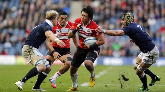 Japan's Shinya Makabe is tackled by Scotland's David Denton and Kelly Brown during their rugby union match in Edinburgh
