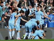 Manchester City's Sergio Aguero celebrates his late winning goal with team-mates during the Premier League match against Queens Park Rangers at The Etihad Stadium in Manchester. Manchester City won the game 3-2 to secure their first title since 1968