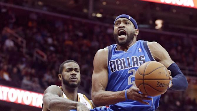 Dallas Mavericks' Vince Carter (25) jumps to the basket against Cleveland Cavaliers' Earl Clark (6) during the second quarter of an NBA basketball game Monday, Jan. 20, 2014, in Cleveland
