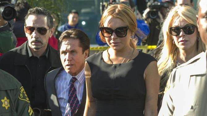 Lindsay Lohan, third from left, her mother Dina Lohan, right, her new attorney Mark Heller, second from left, leave a Los Angeles court, Wednesday, Jan. 30, 2013, in a case filed over the actress' car crash last June. A judge has delayed Lindsay Lohan's trial on three misdemeanor counts. She pleaded not guilty to lying to police, reckless driving and obstructing officers from performing their duties. (AP Photo/Damian Dovarganes)