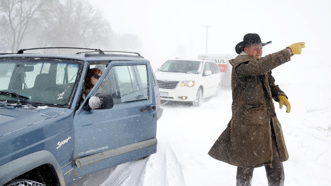 JC Hobbs directs his wife Sarah as they help to pull a van and U-Haul up a hill outside Calhan, Colo. as a storm continued to bring bad weather to the Colorado Springs area Saturday, March 23, 2013.   Transportation officials said Interstate 70 was closed from Denver to Colby, Kan., on Saturday. The National Weather Service said the Denver area could see up to 7 inches of snow Saturday. (AP Photo/The Colorado Springs Gazette, Michael Ciaglo)  MAGS OUT