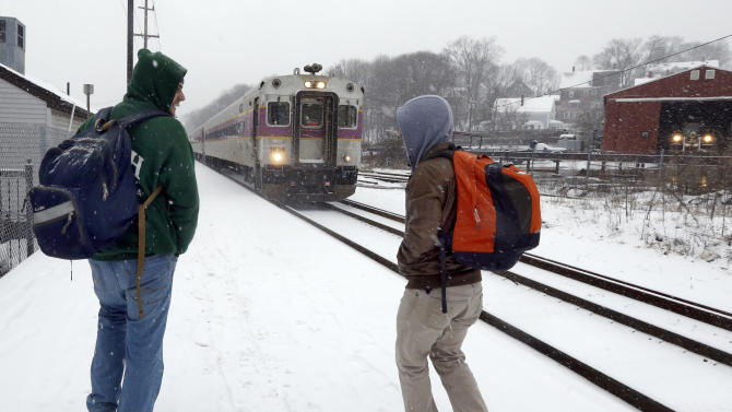 Two travelers walk to catch the last train into Boston from the Andover, Mass. train station as snow falls on Friday, Feb. 8, 2013. A major winter storm is barreling into the U.S. Northeast with up to 2 feet of snow expected for a Boston-area region that has seen mostly bare ground this winter. The MBTA will suspend all transit service in the late afternoon due to the storm. (AP Photo/Elise Amendola)