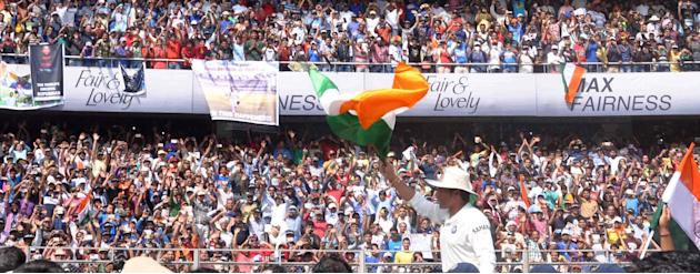 Cricket legend Sachin Tendulkar waves Indian flag as he bids adieu to international cricket after his 200th and the last Test match at Wankhede stadium in Mumbai on Nov.16, 2013. (Photo: Sandeep Mahan