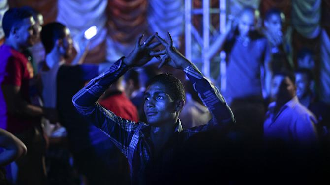 "In this Sunday, June 2, 2013 photo, An Egyptian man dances, as ""Mahraganat"", Arabic for ""festivals,"" singers, Fifty and Sadat, not pictured, perform at a wedding in Madinet el-Salam on the outskirts of Cairo, Egypt. A new musical sound emerged from the underground in Egypt since the country's 2011 revolution, a rapid-fire electronic beat, mixed with hypnotic rhythms drawn from religious festivals and fired up with auto-tuned vocals. Besides getting club crowds dancing all night long, it has given a rebellious voice to long marginalized youth, telling stories of everyday life in beaten-down neighborhoods of Cairo. (AP Photo/Nariman El-Mofty)"