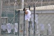 In this file photo, reviewed by a US Department of Defense official, a Guantanamo detainee is seen doing pull-ups inside an exercise area at the detention facility at Guantanamo Bay US Naval Base in Cuba, in 2009. The US government has published for the first time a list of 55 Guantanamo detainees cleared for release but still held at the facility