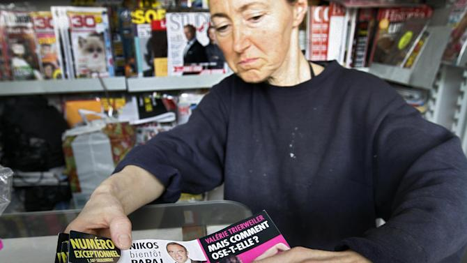 """FILE - In this Sept. 18, 2012 file photo, a news stand worker checks copies of Closer magazine which published 14 photos of a partially clad Kate Duchess of Cambridge in its pages, in Nice, southern France. A prosecutor's office says Thursday, April 26, 2013 a French judge has placed under investigation the photographer and publishing company behind unauthorized topless photos of Prince William's wife, Kate, that appeared in """"Closer"""" magazine in France last September. (AP Photo/Lionel Cironneau, File)"""